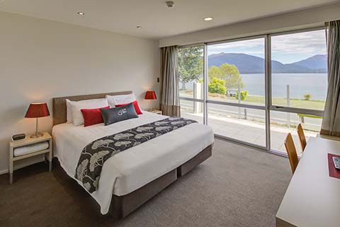 A luxurious king sized bed in a Marakura Motel Studio unit with the magnificent view of Lake Te Anau able to be seen through the window