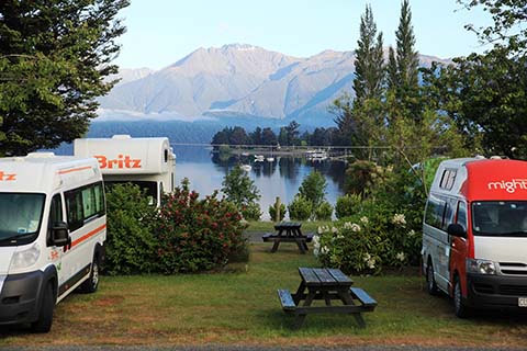 Three campervans parked on grassy powered sites surrounded by lush green plants and Lake Te Anau in the background