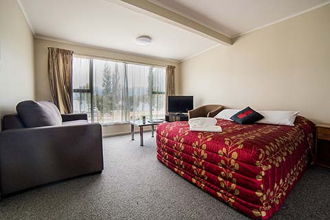 Bed with maroon coloured bed covers in a room which also contains a settee and television
