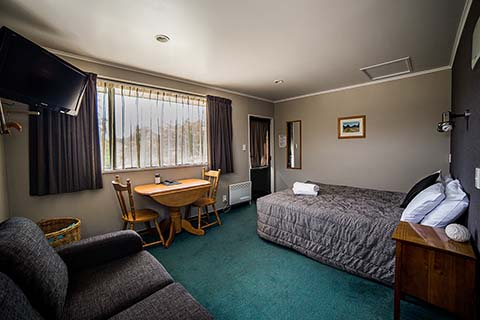 Studio motel room with Bed, small dining table, television and settee