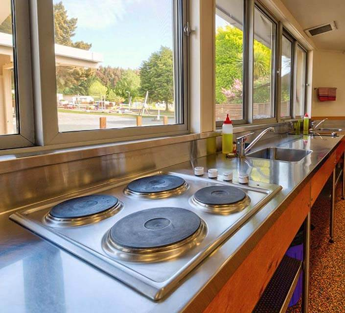 Stainless steel kitchen bench area with two sinks a cooktop