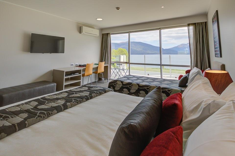 Marakura Family Room unit with a king sized bed and a single bed. Views of Lake Te Anau can be seen through the large window