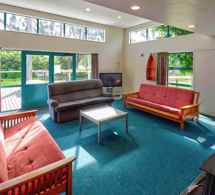 Seating area with three settees and a coffee table in the Steamers Beach Backpackers lounge room area