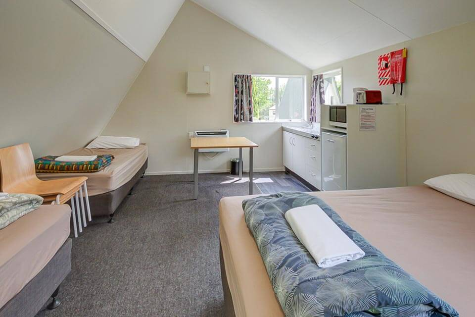 Kitchen Cabin at Te Anau Lakeview Holiday Park containing a Queen bed and two single beds