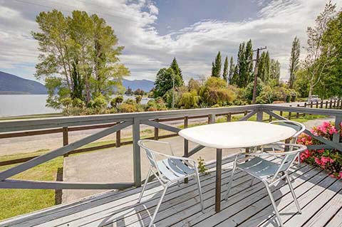 A table and three chairs on the deck of the Koromiko Lodge units, with picturesque Lake Te Anau in the background