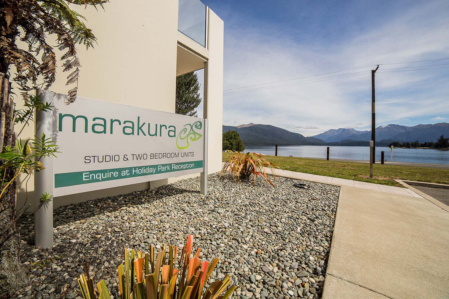 Marakura Motels sign in the foreground with a calm Lake Te Anau and mountains in the background