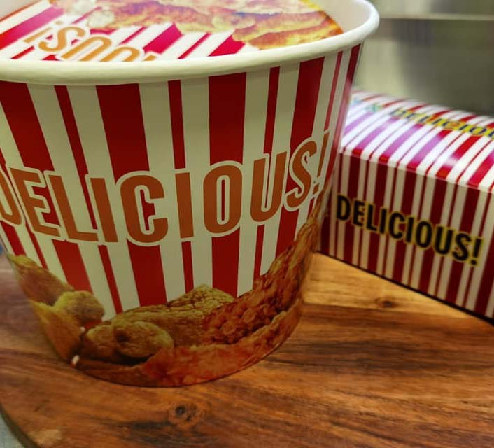 Red & white striped takeaway containers with images of fried chicken on them